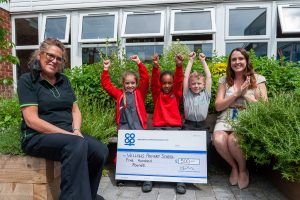 Lichfield Co-op manager handing over cheque from Community Dividend Fund to school