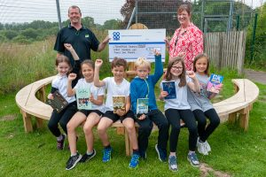 Polesworth Co-op manager presenting Community Dividend Fund cheque to headteacher with pupils holding books and sitting around a circular table