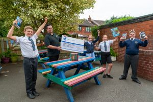 Rosliston Co-op Community Dividend Fund presentation with pupils holding books and cheering