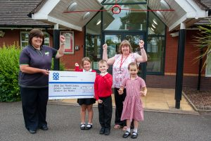 Wood End Co-op manager presents Community Dividend Fund cheque to head with three pupils cheering